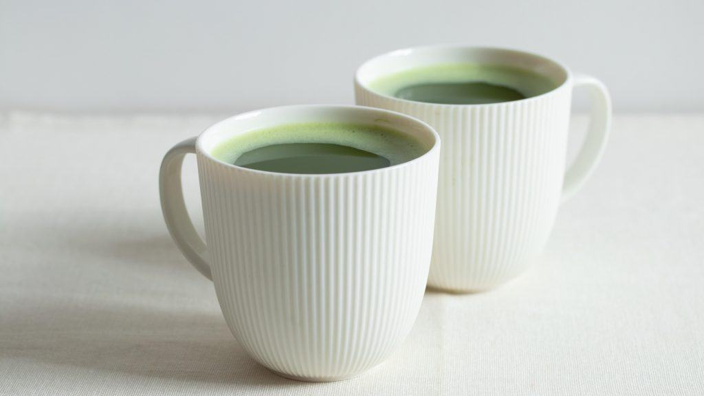 Two cups of matcha tea on light background