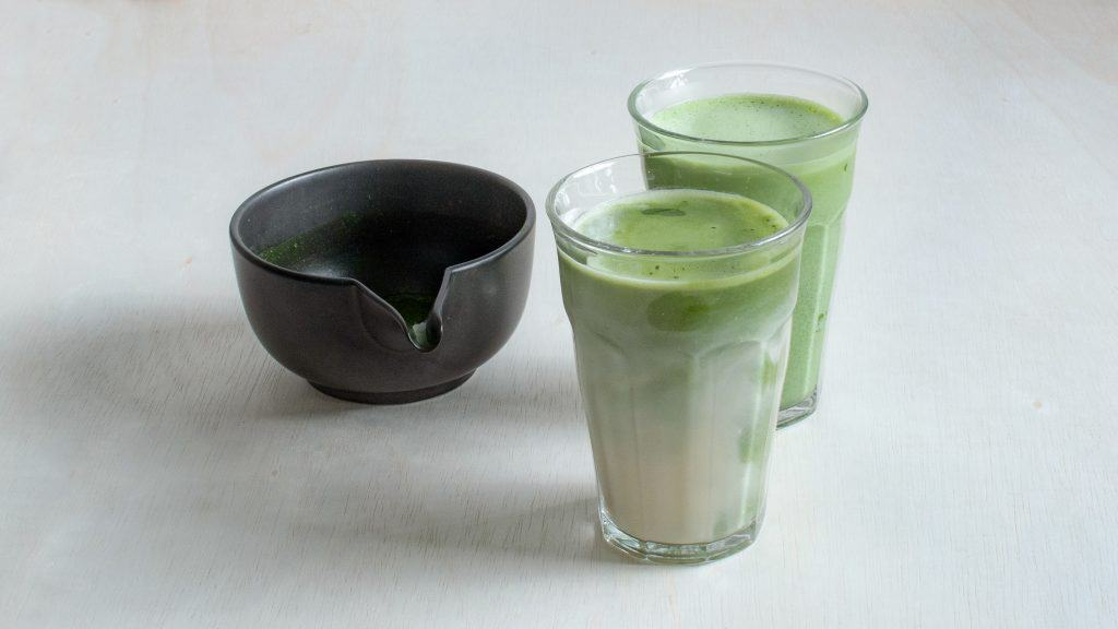 Two glasses of hot matcha oat milk latte