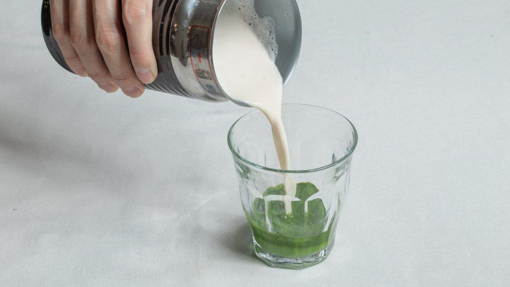 Pouring heated oat milk into glass filled with matcha and water mixture