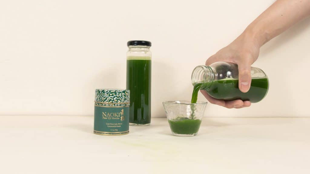 Hand pouring cold brew matcha into glass with Naoki Cold Brew Ceremonial blend