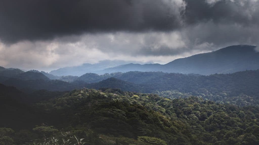 Mountain view of Kagoshima landscape with dark clouds over vast field of greenery