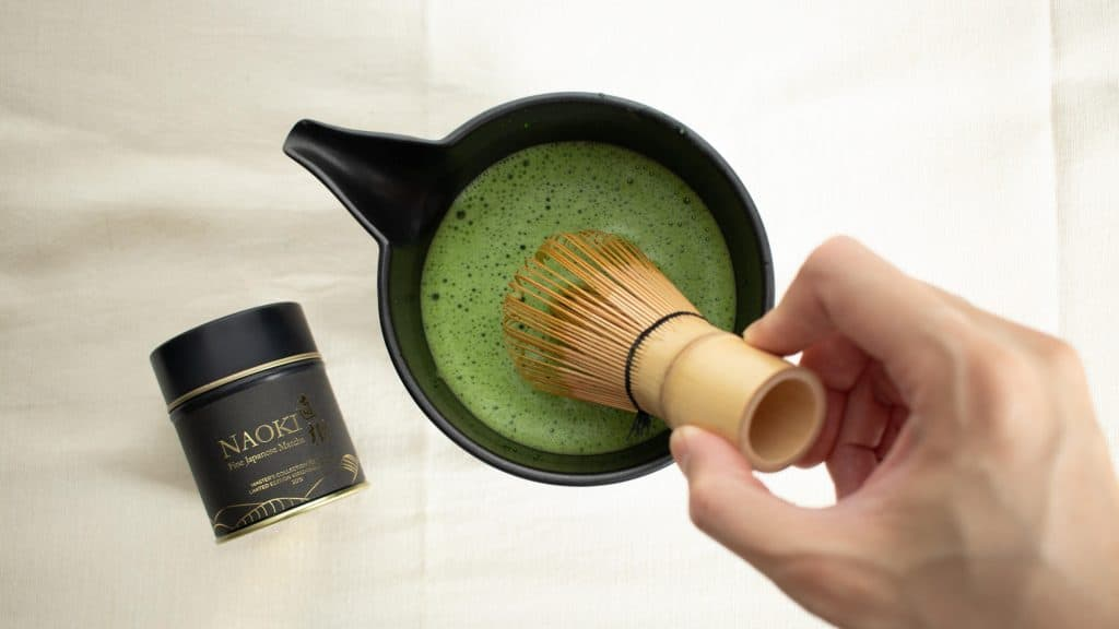 Hand whisking usucha in a bowl with a bamboo whisk using Naoki Master's Collection Organic Kirishima blend