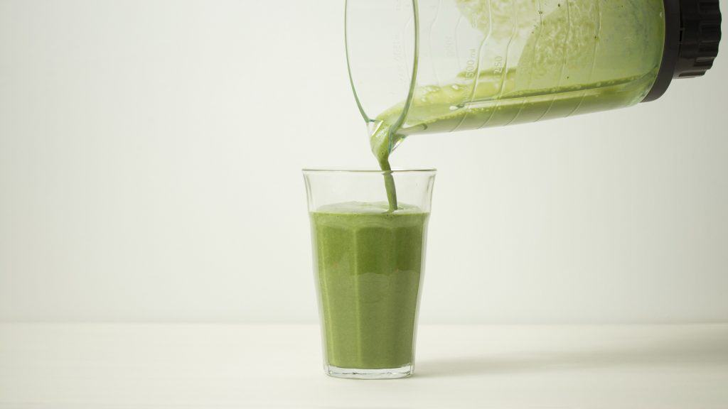 Pouring matcha smoothie into a clear glass