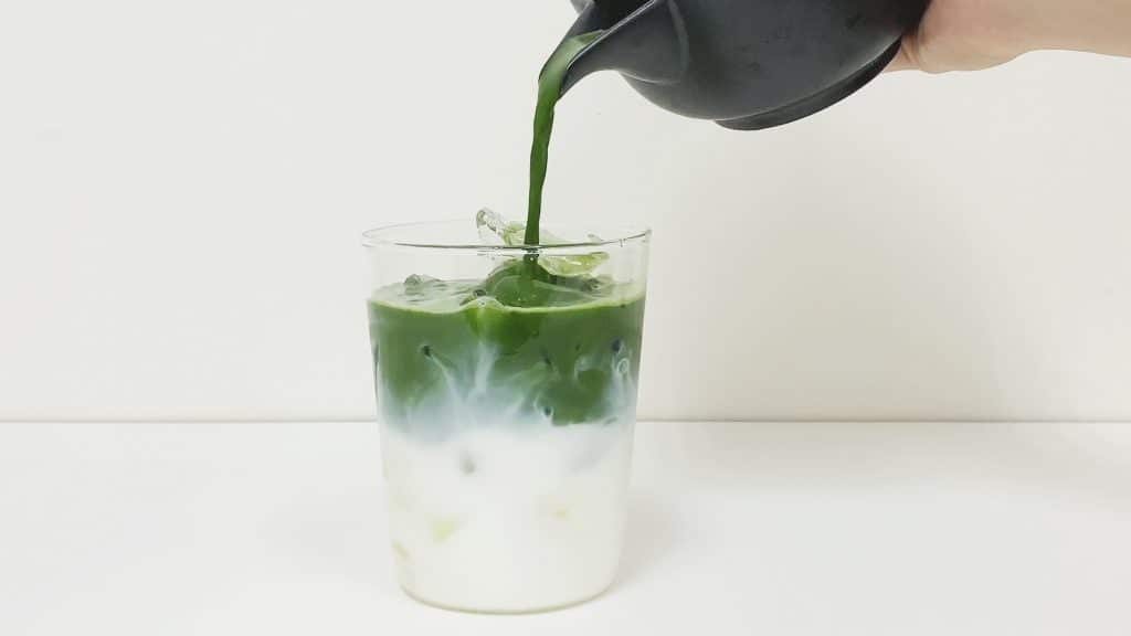 Hand pouring matcha into a glass of layered oat milk and ice