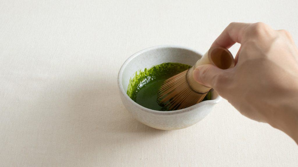 Hand whisking water and bright matcha powder in a small bowl with bamboo whisk