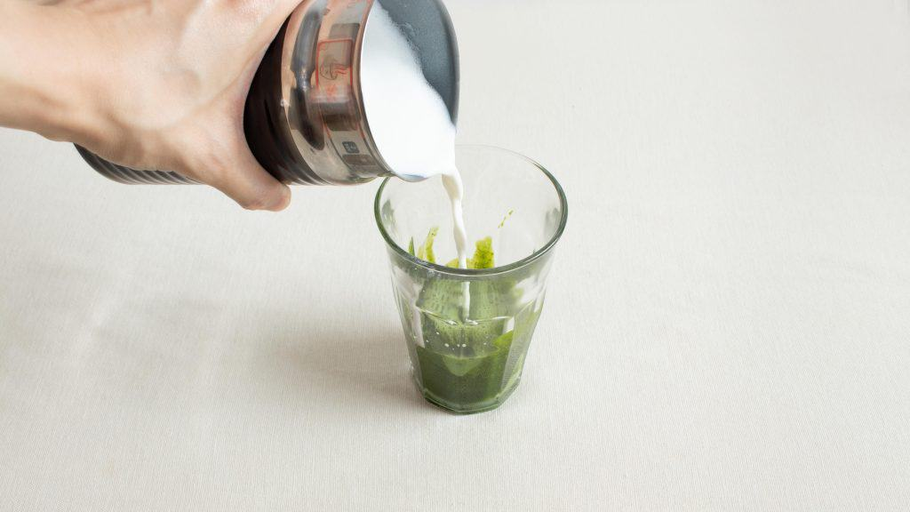 Hand pouring warm fresh milk from bottle into glass of matcha mixture for classic matcha latte