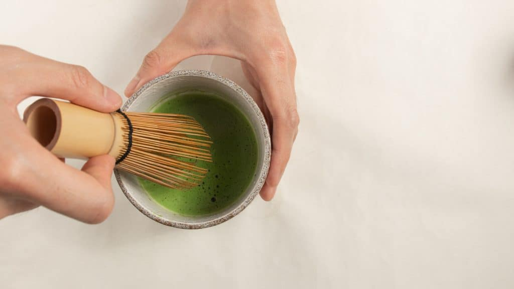 Making matcha tea with bamboo whisk