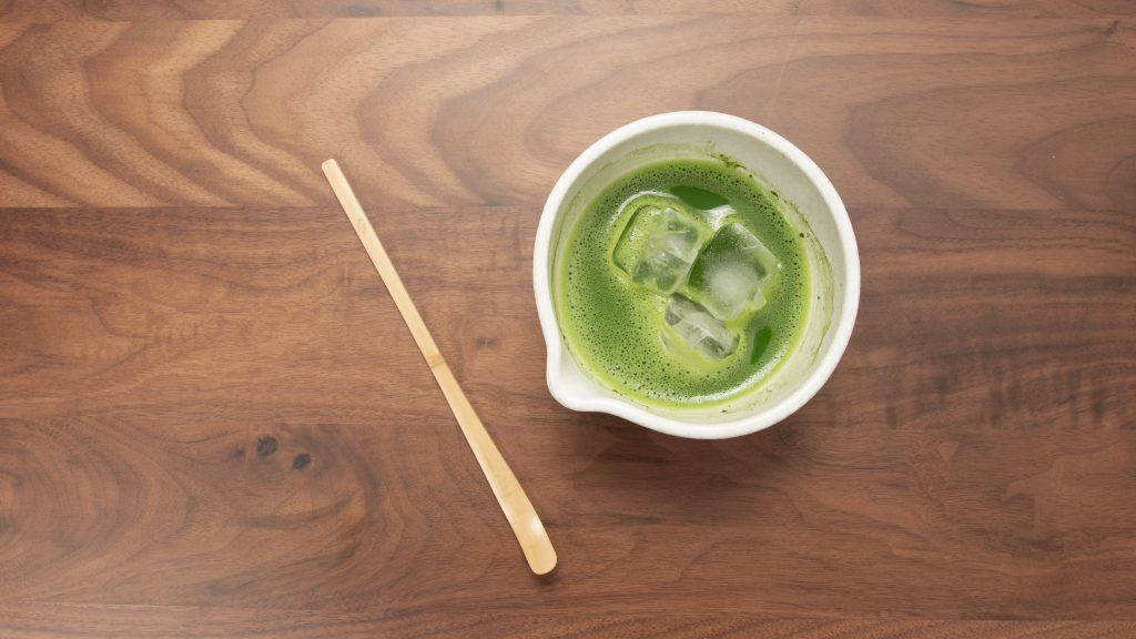 overhead of cold matcha tea with chashaku scoop on wooden table
