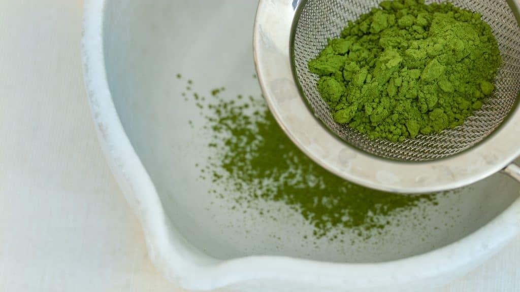 sifting matcha powder with a sift