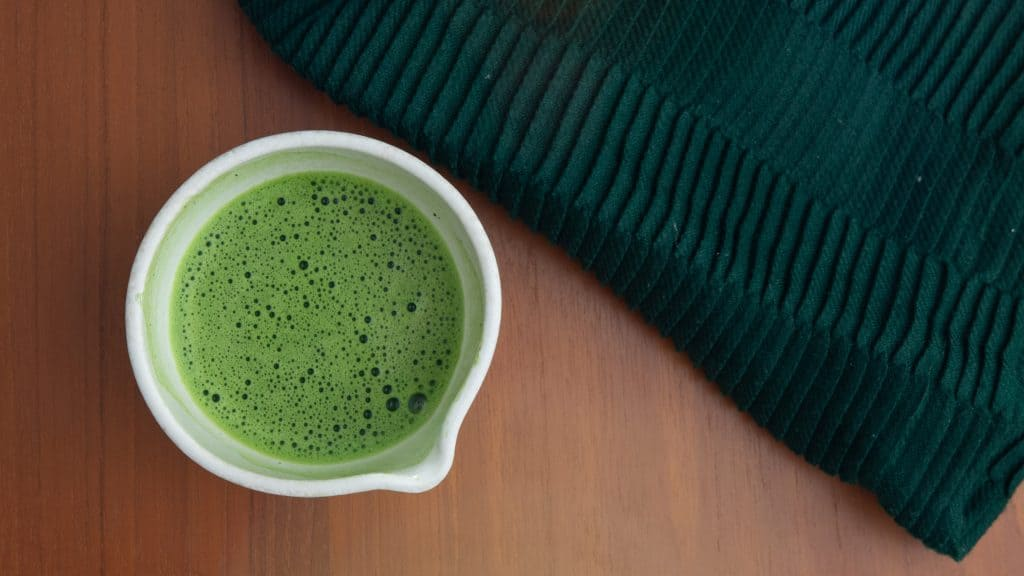 Matcha usucha on wooden table with throw