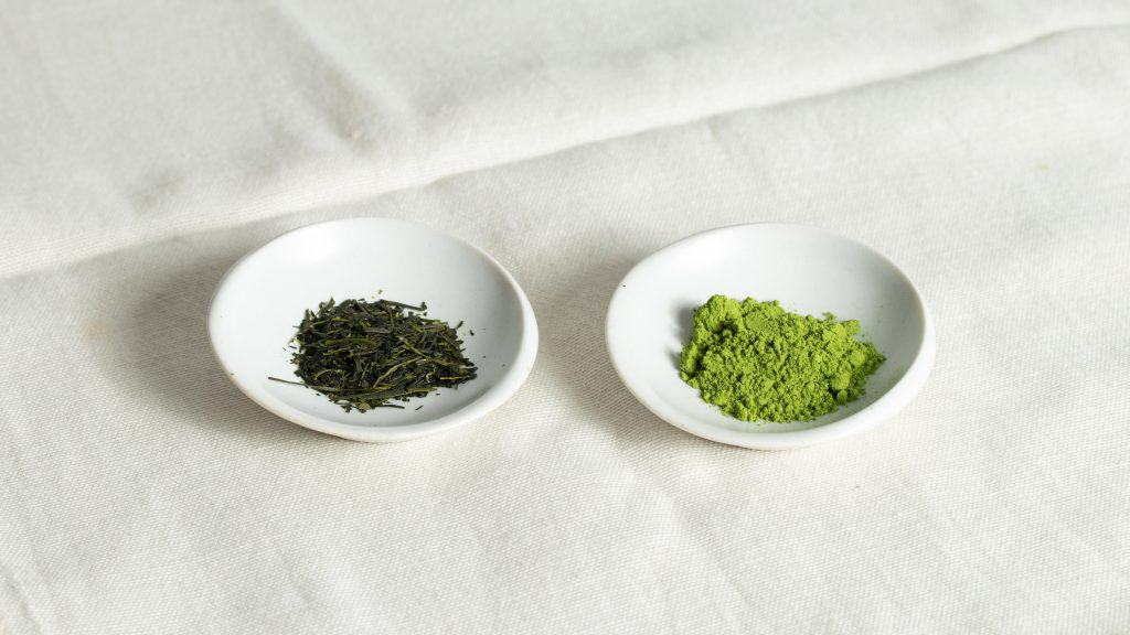Sencha leaves and matcha powder on small white plate