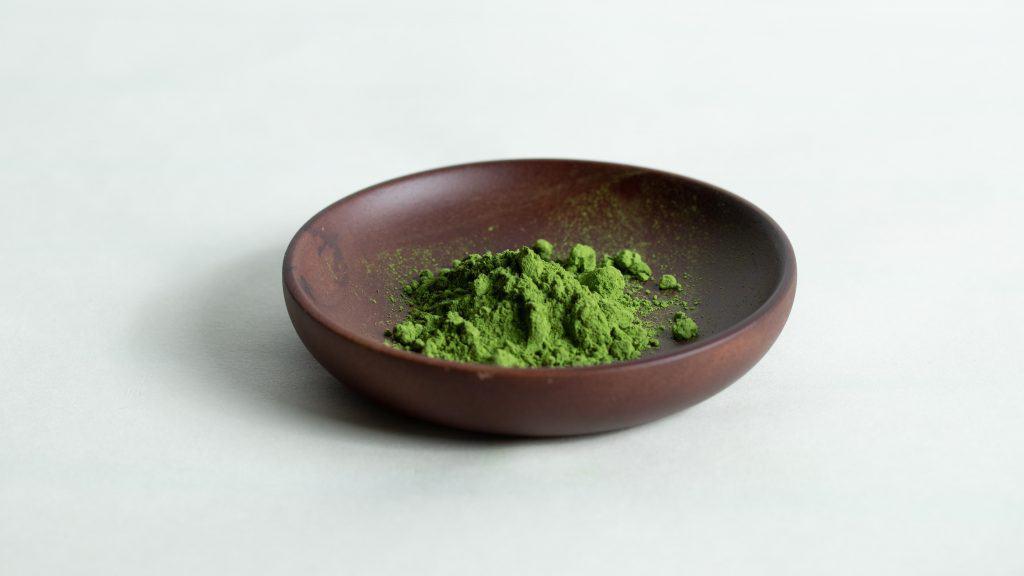 bright green matcha powder on wooden plate