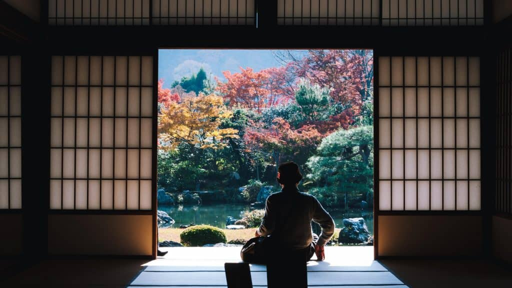 A silhouette of traditional Japanese woman in kimono sitting in between shoji screens