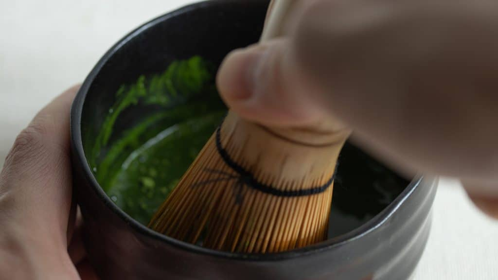 Close view of hand whisking the thick consistency of koicha