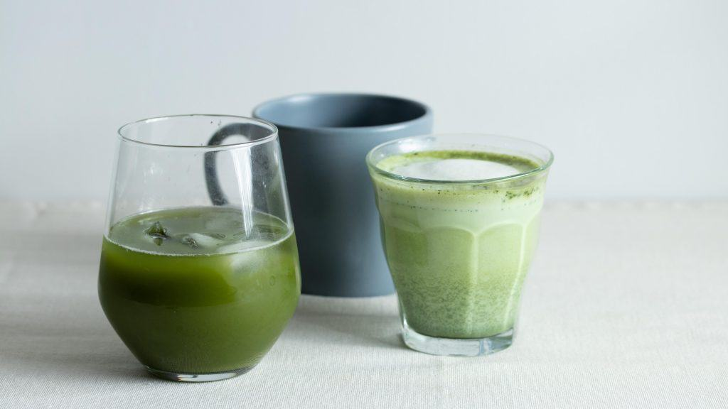 Various matcha drinks - Iced matcha tea in a glass, with frothy matcha latte and a blue mug