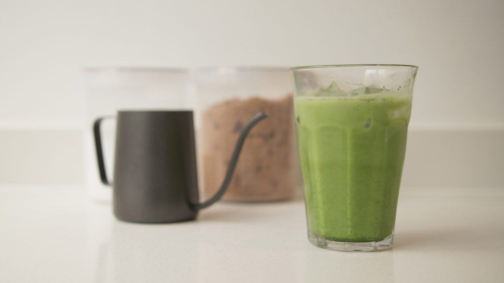 A glass of iced matcha latte with on kitchen countertop
