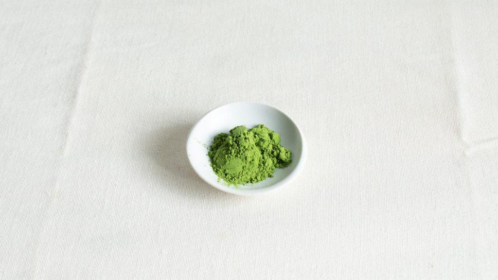 Vibrant green matcha powder on a small white plate