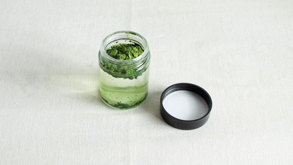 Matcha powder afloat in an open lid jar of water