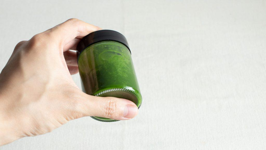 Hand mixing matcha powder with hot water in small jar