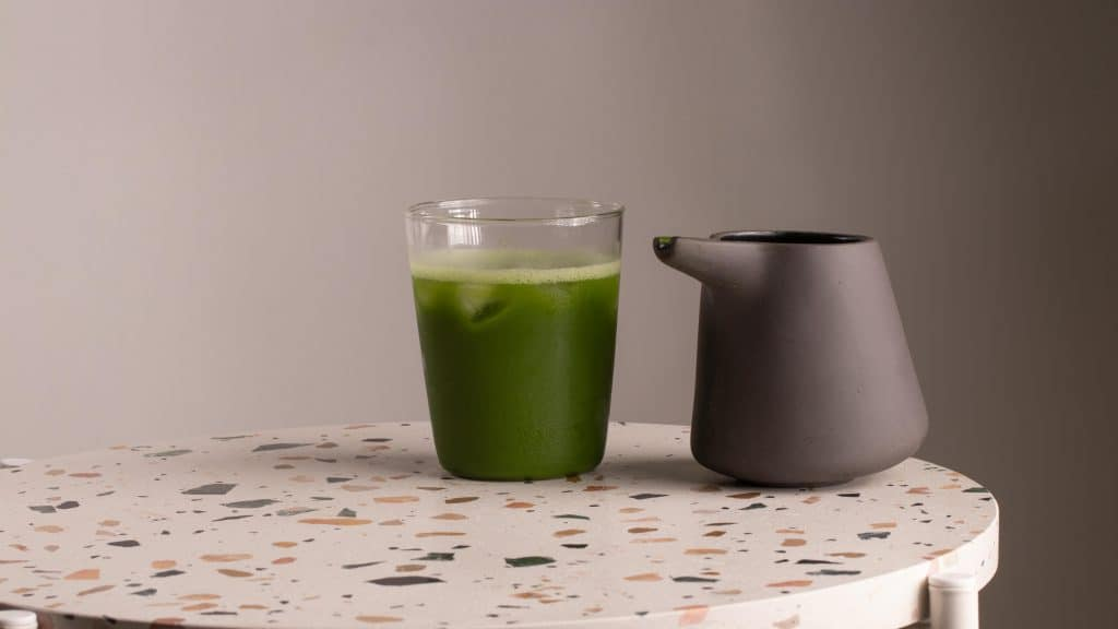a glass of cold matcha tea and a jug on table