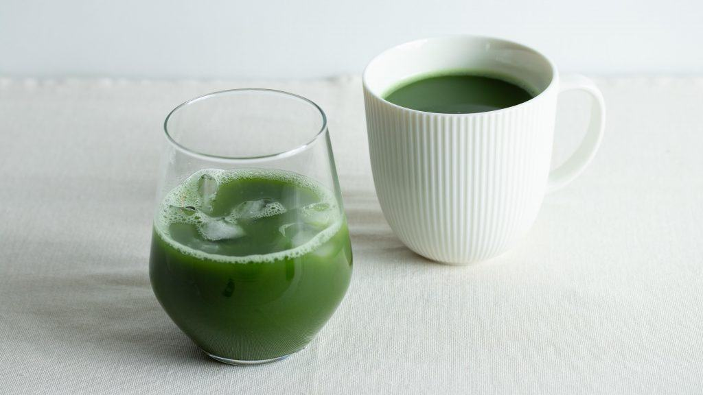 A glass of iced cold brew matcha and a white mug of matcha tea