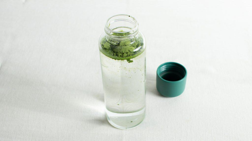 Pour matcha powder in glass bottle filled with water