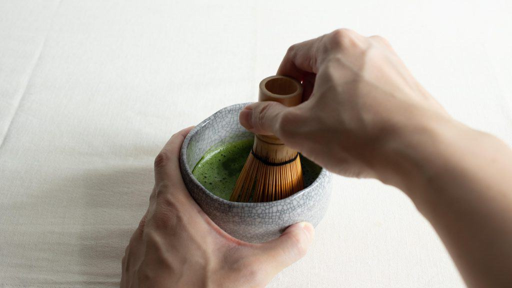 Hand whisking matcha with chasen bamboo whisk in chawan bowl