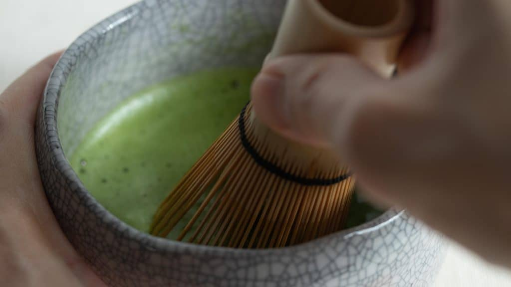 Closeup of hand whisking frothy surface of matcha usucha