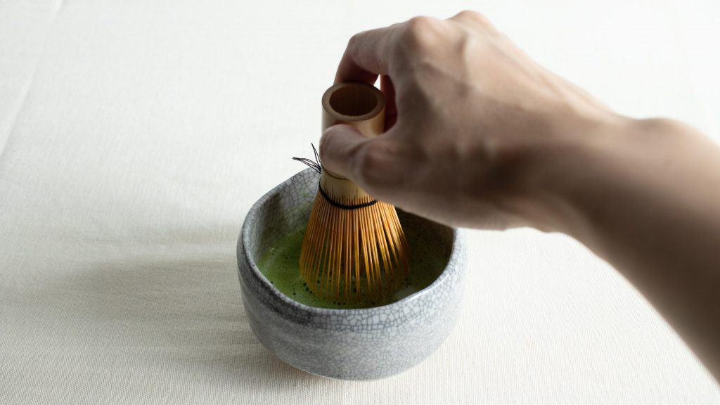 Hand holding chasen in chawan bowl of frothy usucha