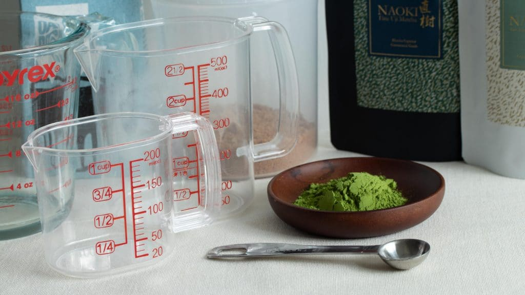 matcha powder on wooden plate with other preparations tools for matcha recipe creation