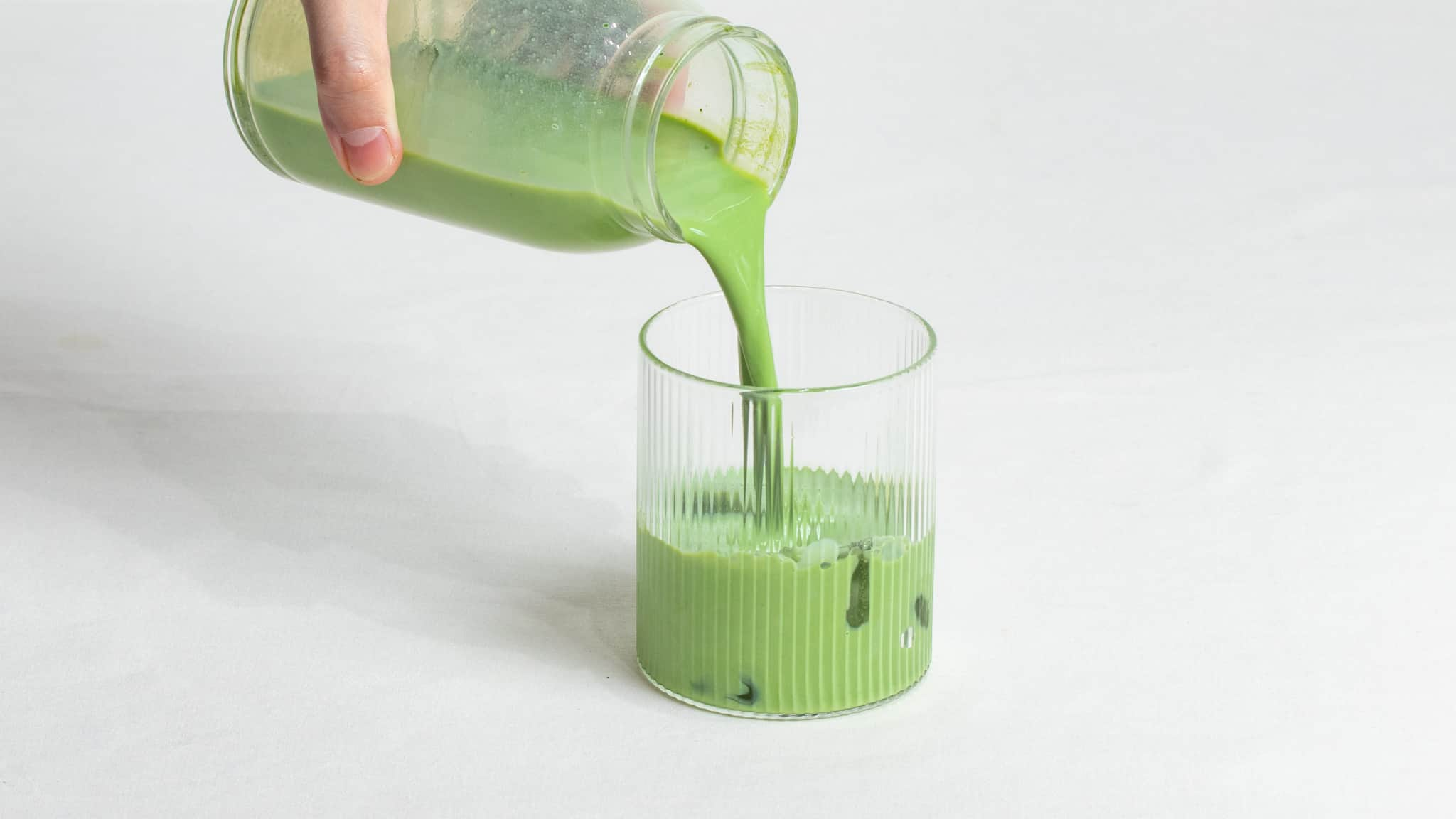 Hand pouring iced matcha latte into glass