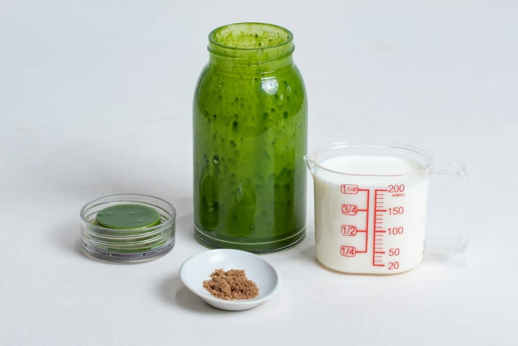 Matcha in an uncapped glass bottle with fresh milk in measuring cup and brown sugar