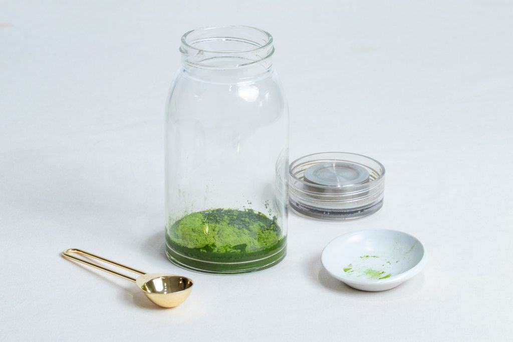 Matcha powder in a glass bottle with measuring teaspoon to make iced matcha latte