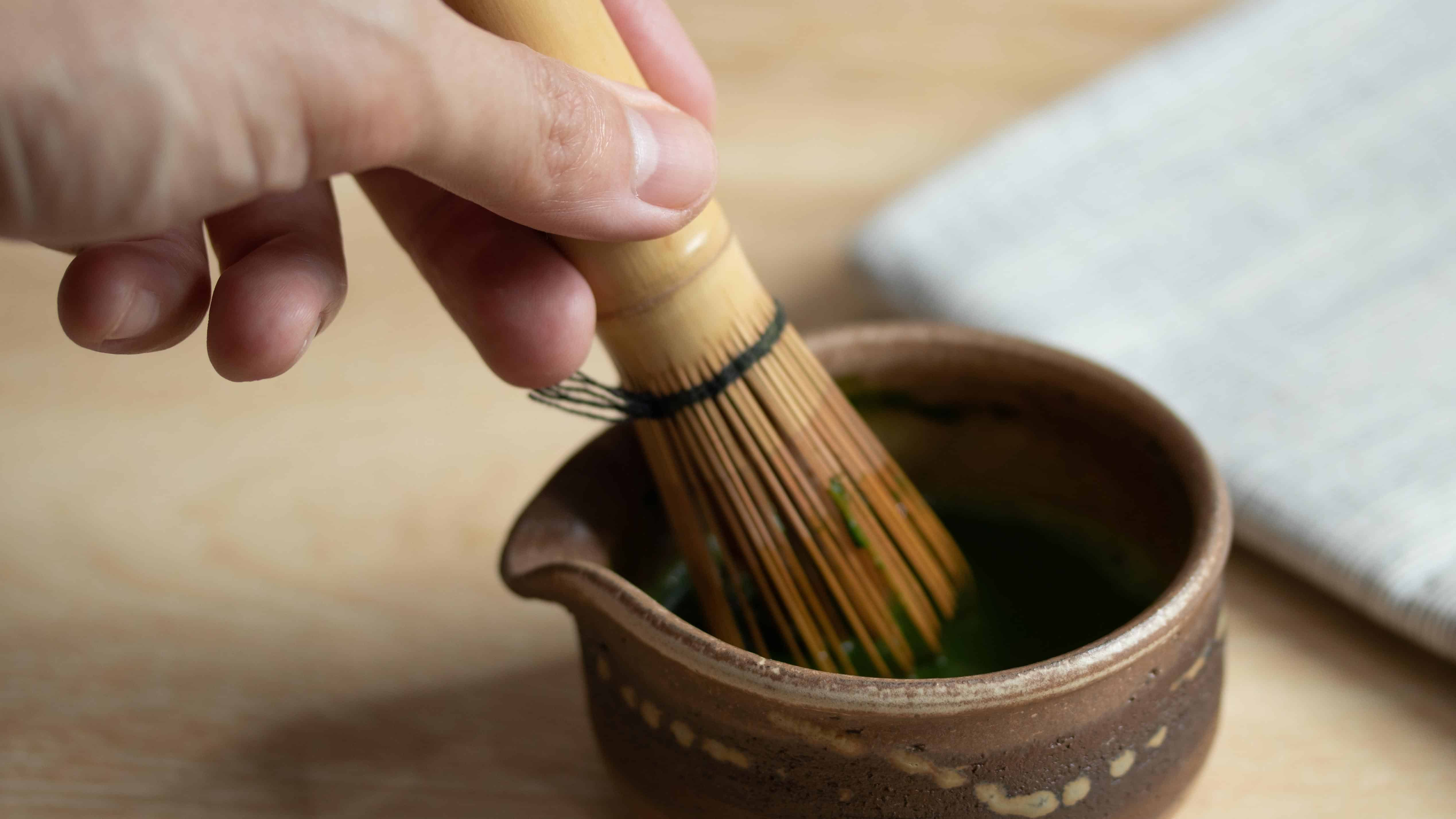 Whisking matcha powder and water with bamboo whisk in a bowl
