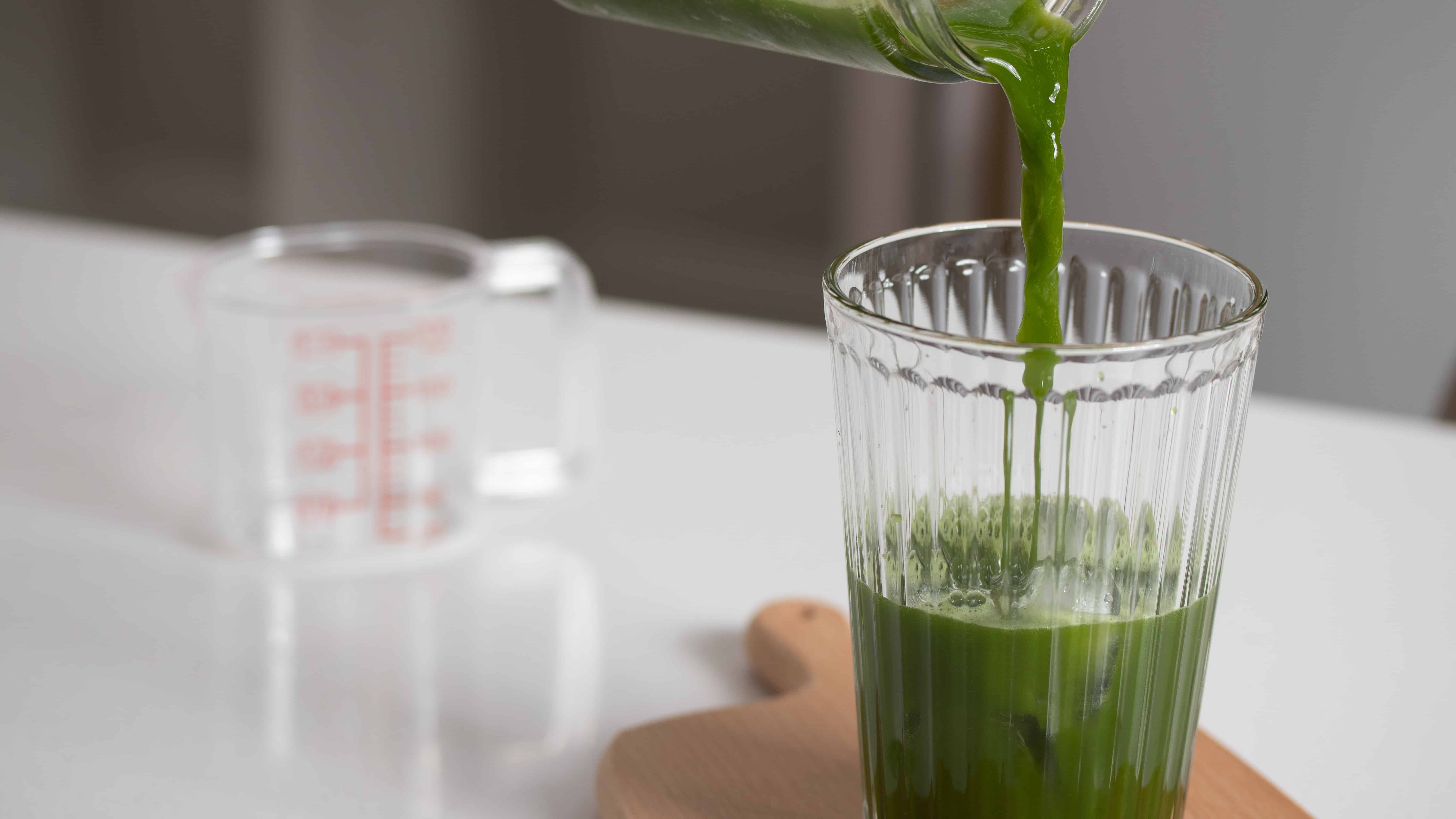 pouring matcha tea into a glass of iced for matcha float